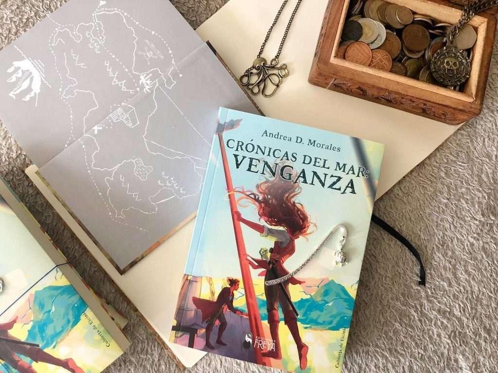 Fotografía del libro acompañado de un colgante en forma de kraken en color dorado, un marcapáginas metálico con adorno de tortuga en plateado, un mapa decorativo, un cofre con monedas y un colgante de pirata